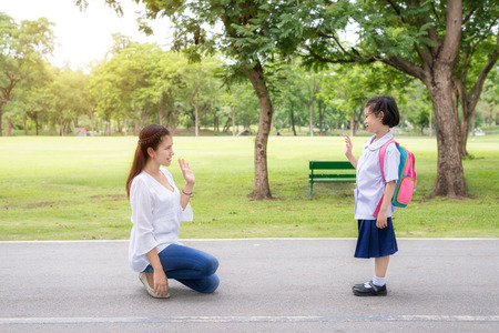 Back to school. Asian mother say goodbye to daughter student in park at school before study. Asian mother sent hand sign to goodbye.