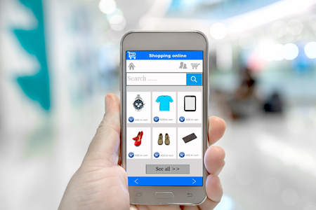 Photo pour Smart phone online shopping in man hand. Shopping center in background. Buy clothes shoes accessories with e commerce online shopping website - image libre de droit