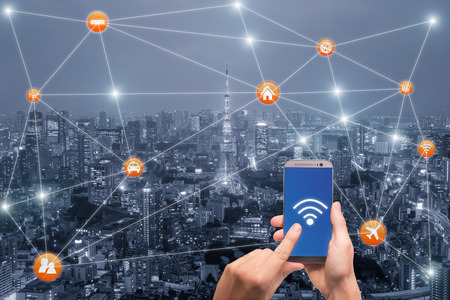 Foto de Hand holding smartphone with Tokyo city scape and wifi network connection. Smart city network connection concept - Imagen libre de derechos