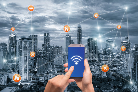 Photo pour Hand holding smartphone with bangkok city scape and wifi network connection. Smart city network connection concept - image libre de droit