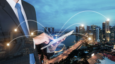 Foto de Double exposure of businessman using digital tablet pc with network connection of Singapore city. Network connection concept - Imagen libre de derechos