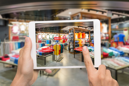 Foto de Augmented reality marketing concept. Hand holding digital tablet smart phone use AR application to check special sale price in retail fashion shop mall - Imagen libre de derechos
