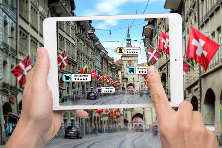 Photo pour Hand holding smart phone use AR application to check relevant information about the spaces around customer. Bern City in background. Augmented reality marketing concept. - image libre de droit