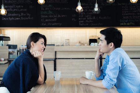 Foto de Dating in a cafe. Beautiful Asian lover couple sitting in a cafe enjoying in coffee and conversation. Love and romance. - Imagen libre de derechos