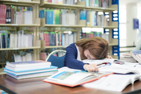Tired Asian student or young woman with many books sleeping while reading book prepare examination in library at university. People, education, session, exams and school concept