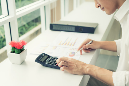 Photo pour Asian business man using a calculator to calculate the numbers on his desk. Accountant calculating finances. - image libre de droit