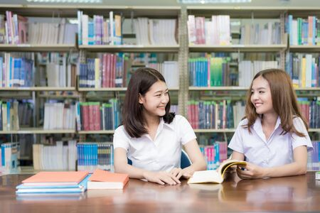 Photo pour Two Asian students studying together in library at university. University student. - image libre de droit