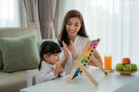 Photo pour Happy Asian young mother and daughter playing with abacus, early education at home. - image libre de droit