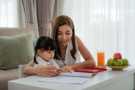 Photo pour Asian mother playing with her toddler drawing together with color pencils at table in living room at home. - image libre de droit