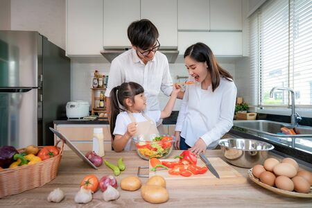 Foto de Asian daughters feeding salad to her mother and her father stand by when a family cooking in the kitchen at home.  Family life love relationship, or home fun leisure activity concept - Imagen libre de derechos