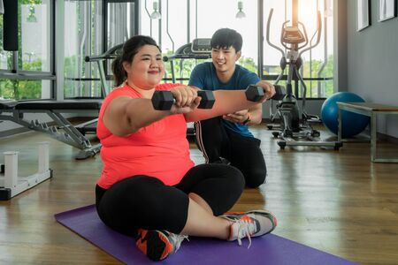 Foto de Two Asian trainer man and Overweight woman exercising with dumbbell together in modern gym, happy and smile during workout. Fat women take care of health and want to lose weight concept. - Imagen libre de derechos