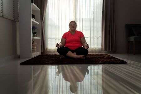 Asian Overweight woman exercising yoga Easy Pose alone on the floor in house, yoga meditation exercise at home. Fat women take care of health and want to lose weight concept.