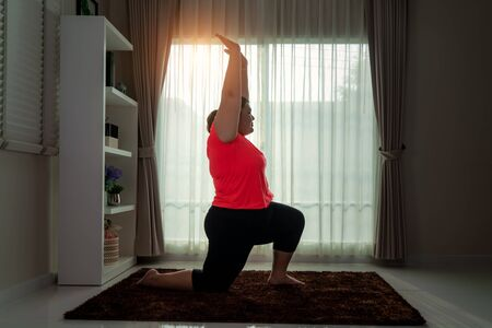 Asian Overweight woman exercising yoga High Lung pose alone on the floor in house, yoga meditation exercise at home. Fat women take care of health and want to lose weight concept.