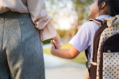 Photo pour Close up of Happy Asian mother and daughter preschool student walking to school. Beginning of lessons. First day of fall. Parenthood or love and bonding expression concept. - image libre de droit