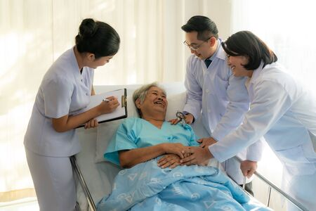Asian medical team of doctors examining and talking to Asian elderly woman patient, health care people take note on clipboard in hospital. Elderly patient care and health lifestyle, medical concept.