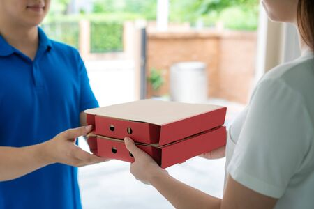 Photo for Asian delivery young man in blue uniform smile and holding pizza boxes in front house and Asian woman accepting a delivery of pizza boxes from deliveryman. Advertising, Business, Transportation Concept. - Royalty Free Image