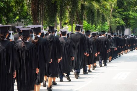 Photo pour Rear view of group of university graduates in black gowns lines up for degree in university graduation ceremony. Concept education congratulation, student, successful to study. - image libre de droit