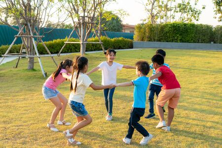 Photo pour Large group of happy Asian smiling kindergarten kids friends holding hands playing and dancing play roundelay and stand in circle in the park on the green grass on sunny summer day. - image libre de droit