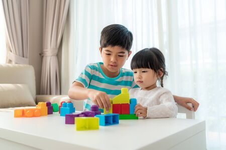 Photo for Asian cute brother and sister play with a toy block designer on the table in living room at home. Concept of bonding of sibling, friendship and learn through play activity for kid development. - Royalty Free Image