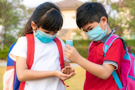 Foto de Asian boy student wear hygienic mask and press alcohol gel from bottle to hand's sister for protect  covid-19 coronavirus and epidemic virus after back from school.  - Imagen libre de derechos