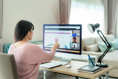 Foto de Asian business woman talking to her colleagues about plan in video conference. Multiethnic business team using computer for a online meeting in video call. Group of people smart working from home.  - Imagen libre de derechos