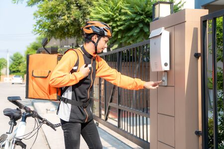 Photo for Asian delivery rider young man in orange uniform with delivery box and bicycle and ringing customers door bell in front house village with copy space. Advertising, Business, Transportation Concept. - Royalty Free Image