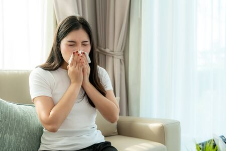 Photo pour Asian woman sick and sad with sneezing on nose and cold cough on tissue paper because influenza and weak or virus bacteria from dust weather or smoke for medical. - image libre de droit