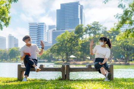 Photo pour Asian young man and woman greet and say hello with they friend and wearing mask sitting distance of 6 feet distance protect from COVID-19 viruses for social distancing for infection risk in park. - image libre de droit