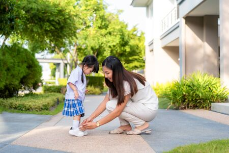 Foto de Asian mother helping her daughter put shoes on or take off at outdoor park getting ready to go out together or coming back home from school in happy family with kids concept. - Imagen libre de derechos