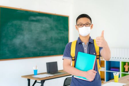 Photo for Asian primary students boy thumb up and  wearing masks to prevent the outbreak of Covid 19 in classroom while back to school reopen their school, New normal for education concept. - Royalty Free Image