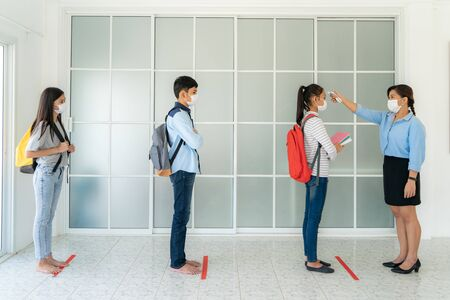 Photo pour Three Asian student wearing mask standing distance of 6 feet from other people keep distance while teacher using thermometer temperature screening student for fever while student coming back to school. - image libre de droit