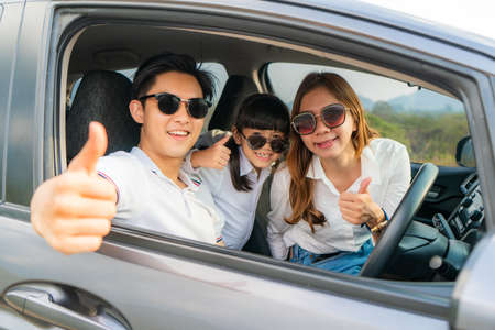 Photo pour Happy Asian family with father thumb up and mother and daughter wear sunglass in compact car are smiling and driving for travel on vacation. Car insurance or rental   - image libre de droit