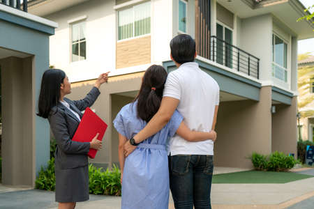 Photo pour Asian woman Real estate broker agent showing a house project detail in her file to the young Asian couple lover looking and interest to buy it. Buying a new house. - image libre de droit