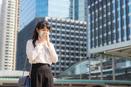 Photo pour Young Asian businesswoman in white shirt going to work feeling sick with cough wears protection mask prevent PM2.5 dust, smog, air pollution and COVID-19 with business office building in Bangkok, Thailand. - image libre de droit