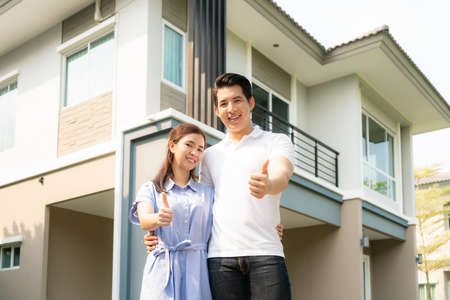 Photo for Portrait of Asian young couple standing, hugging and showing thumb up together looking happy in front of their new house to start new life. Family, age, home, real estate and people concept. - Royalty Free Image