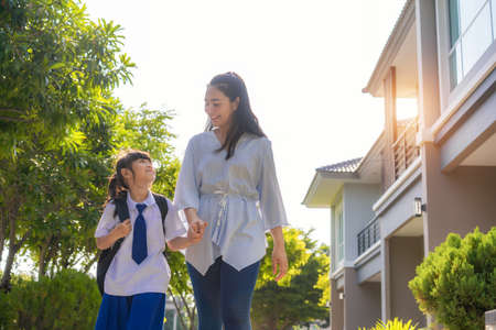 Photo pour Happy Asian mother and daughter primary school student walking to school in the morning school routine for day in the life getting ready for school. - image libre de droit
