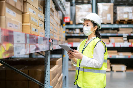 Photo for Young asian woman auditor or trainee staff wears mask working during the COVID pandemic in store warehouse shipping industrial. looking up and checks the number of items store by digital tablet. - Royalty Free Image