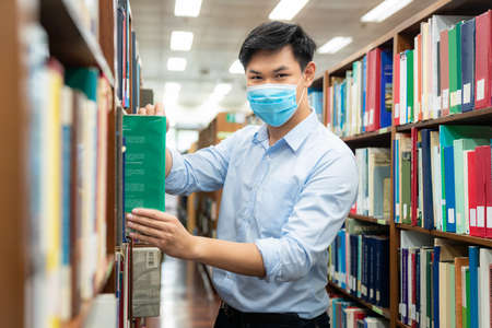 Foto de Asian university student boy wearing face protective medical mask for protection from virus disease reading book at library. Education, high school, university, learning and people concept - Imagen libre de derechos