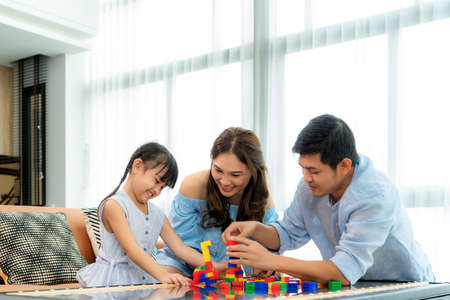 Foto de Asian family spends time in playroom with father, mother and daughter with toys on room background build out of plastic blocks in living room at home - Imagen libre de derechos
