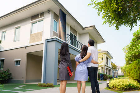 Photo pour Asian woman Real estate broker agent showing a house detail in her file to the young Asian couple lover looking and interest to buy it. Buying a new house. - image libre de droit