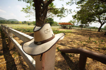 cowboy hat, light brown cowboy hat hanging on farm fence