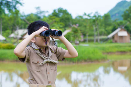 Boy Scout, a Thai Asian young boy scout in uniform exploring with binocular in the forest