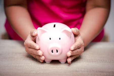 Photo pour Woman hand holding pink piggy bank for saving money prepare financial management in the future, concept business saving money and investment growth professional. - image libre de droit
