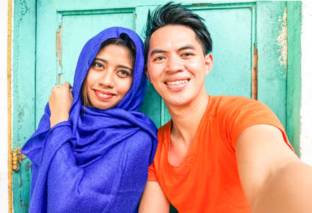 Young asian muslim couple taking selfie next to old green wooden door - Cheerful teenagers of different religion posing for self photo - Portrait of mixed culture students - Focus on male subject