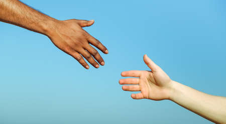 Photo for Black hand man helping white person - Different skin color hands united against racism and racial problem - Concept of humane aid between different cultures and religion - friendship between peoples - Royalty Free Image