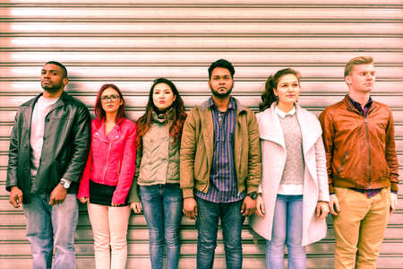 Photo pour Multiracial serious people lineup as mugshot is standing next to metal rolling shutter - Unemployed multi ethnic friends line up outdoor - Concept of discrimination and youth concern for the future - image libre de droit