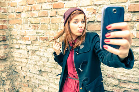 Young pretty woman taking selfie outdoors - Female winter fashion portrait - Teenager student holding mobile phone for selfi photo next to brick wall background - Soft and hazy vintage filtered lookの写真素材