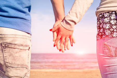 Holding hands on beach at sunrise - Young couple in love looking sunrise on ocean - Romantic scene at sunset - Concept of loving human relationship - Sun light halo and vintage filter with warm tones
