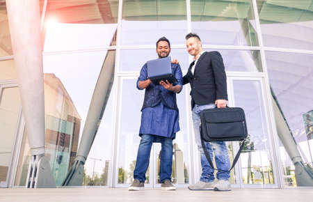 Young indian businessman showing work-plan at colleague - Cheerful men with laptop standing outside business building - Concept of global market and multiethnic cultures working everyday together