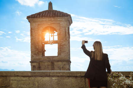 Silhouette of woman taking photo with smart phone of old bell tower at sunset - Back view of female tourist shooting church steeple - Concept of tourism and technology - Backlit image soft vignetting